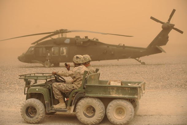 US Army soldiers drive past a Blackhawk helicopter in Kandahar, March 27, 2011.