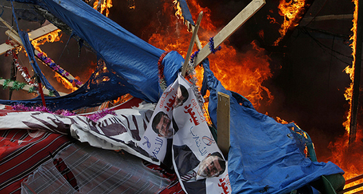 A protest tent burns as Egyptian security forces moved in to disperse supporters of Egypt's ousted president Mohamed Morsi by force in a huge camp near Rabaa al-Adawiya mosque in eastern Cairo on August 14, 2013.