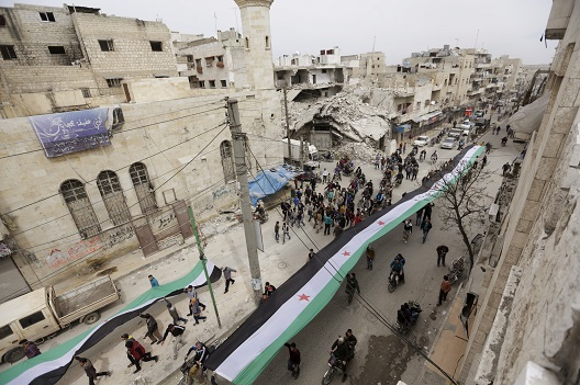 Protesters carry opposition flags as they march along a street during an anti-government protest in the rebel-controlled area of Maaret al-Numan town in Idlib province, Syria March 25, 2016. REUTERS/Khalil Ashawi