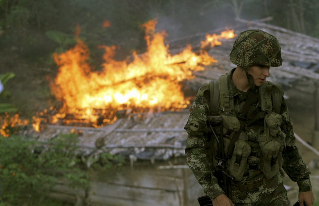 A soldier from the Seventh Division of the Colombian National Army looks on as a make-shift cocaine laboratory burns during an operation to eradicate coca plants in Yali, Antioquia, Colombia. Addressing the world drug problem requires tackling the issue at all stages of the production process. (REUTERS/Fredy Builes)