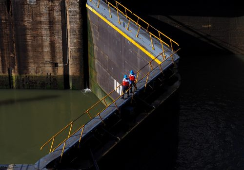 Two men walking across a floodgate.