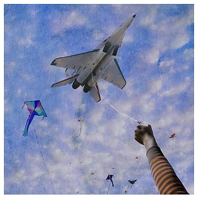 An image designed like an old photo aimed skyward, where a child's outstretched arm holds a fighter jet attached to a string among a smattering of kites.