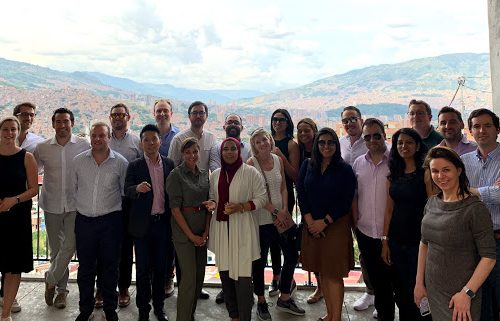 Group of Millennium Fellows standing in front of Medellin backdrop