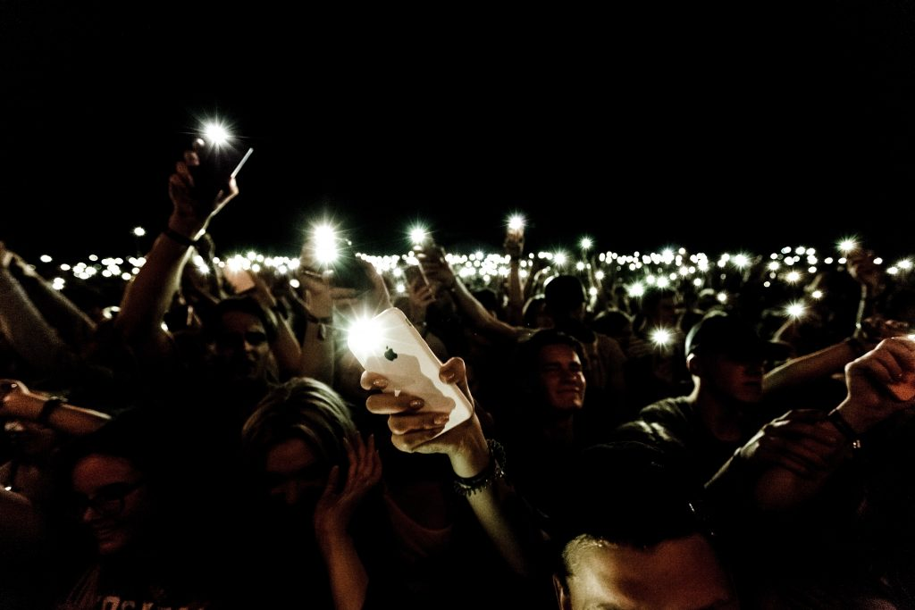 people holding luminated smartphones in the air at night