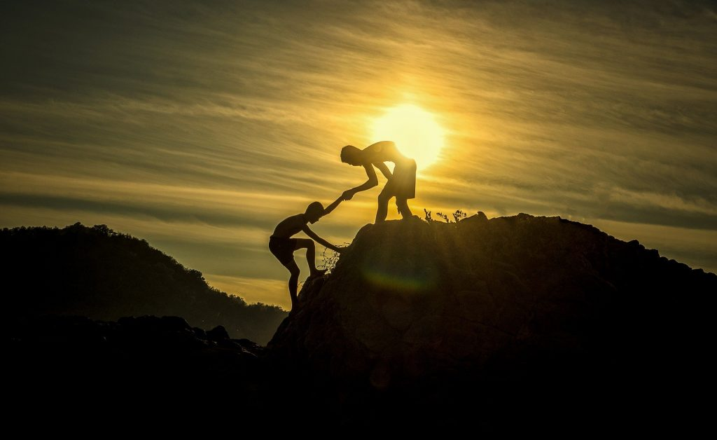 gtc helping hands of two people climbing a mountain together
