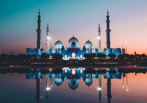 Summertime sunset photo of white concrete mosque in Abu Dhabi
