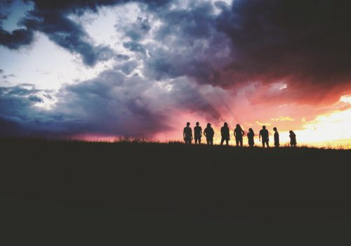 gtc photo of nine people standing on a hill with beautiful clouds in the background