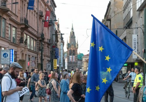 People walking on the road in Prague, Czech Republic, with an EU flag in the foreground