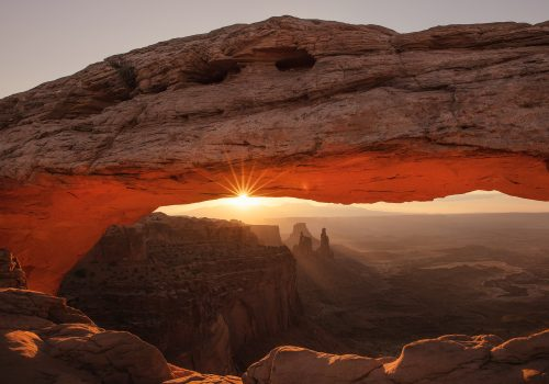 gtc photo of sun peaking through a large rock formation