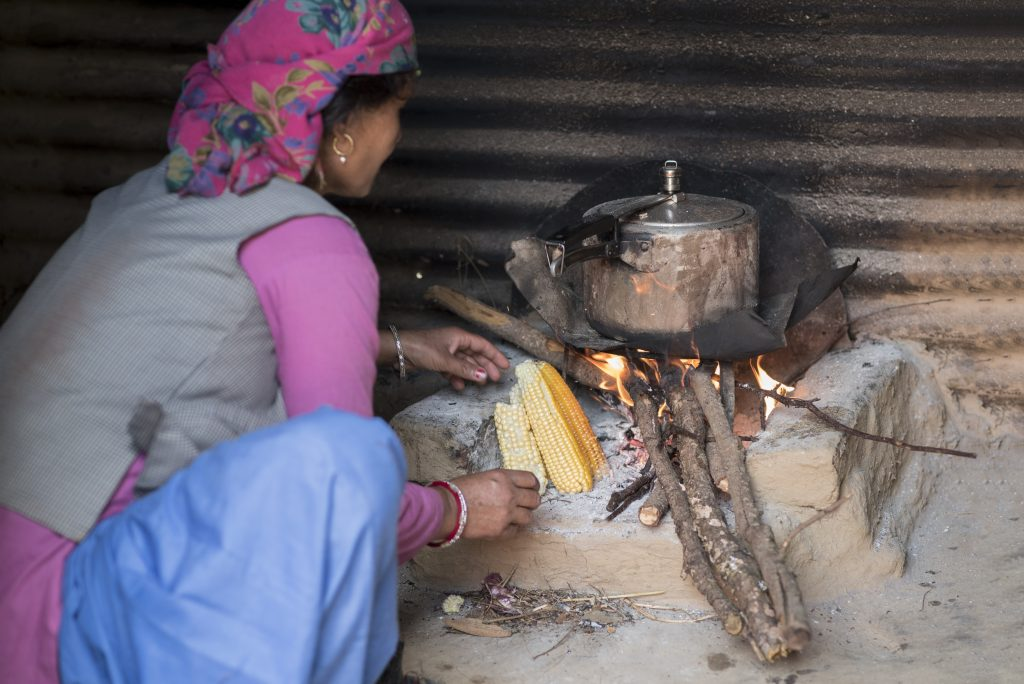 woman cooking over wood fire