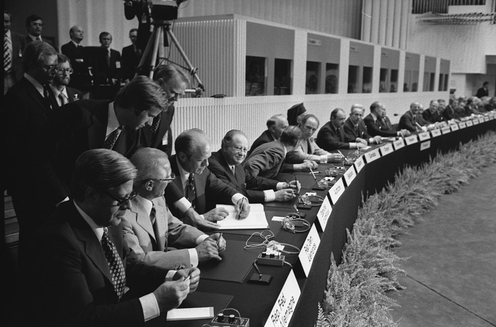 Photograph of President Gerald R. Ford Signing the Final Act of the Conference on Security and Cooperation in Europe as It is Passed Among European Leaders for Signature in  Finlandia Hall in Helsinki, Finland